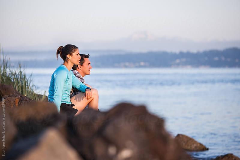 Couple sitting on the beach enjoying the scenery by Suprijono Suharjoto for Stocksy United