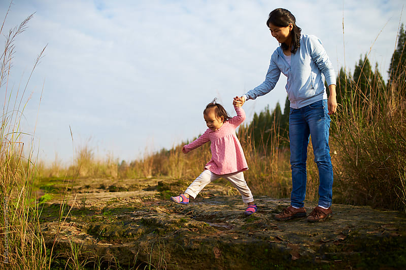 happy little asian girl with her mother outdoor in the autumn sunshine by cuiyan Liu for Stocksy United