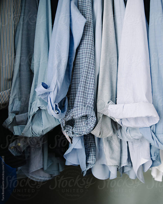 the rolled cuffs of a closet full of men's blue button-down shirts by Tara Romasanta for Stocksy United