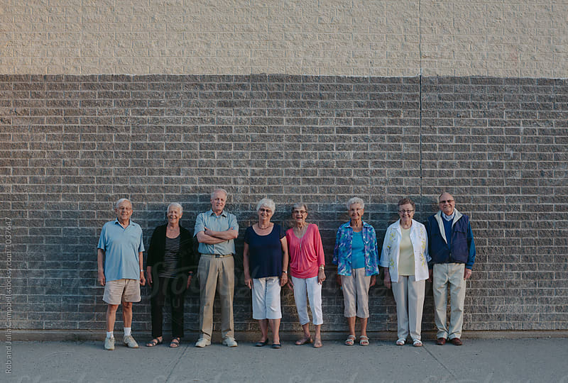 Fun portrait of happy caucasian seniors outside at schoolyard brick wall by Rob and Julia Campbell for Stocksy United