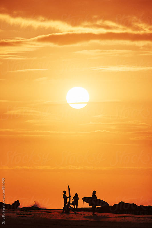 A group of surfers stand silhouetted against a bright orange sunset by Gary Parker for Stocksy United