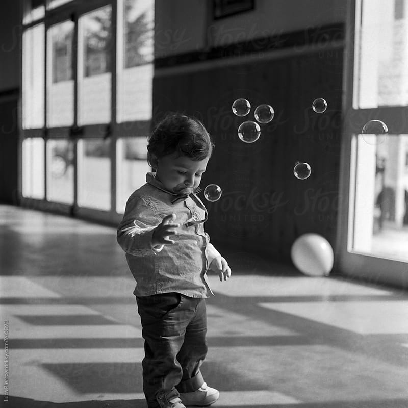 Little dude playing with soap bubbles by Luca Pierro for Stocksy United
