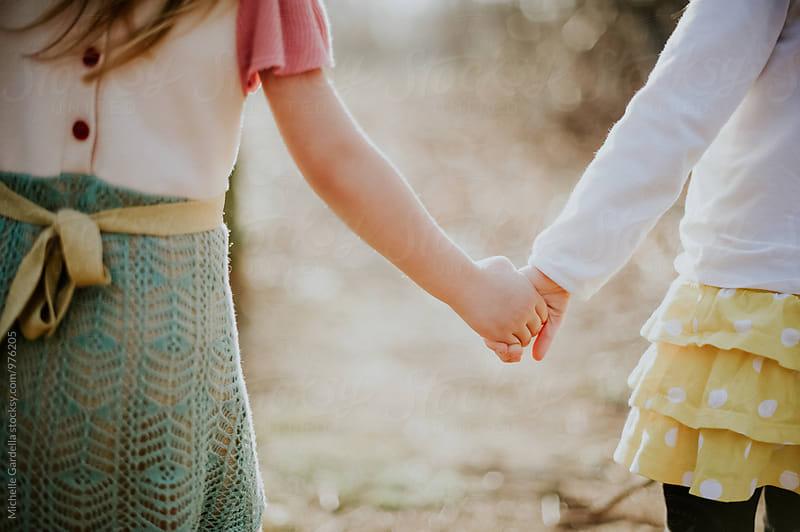 little children friends holding hands by Michelle Gardella for Stocksy United