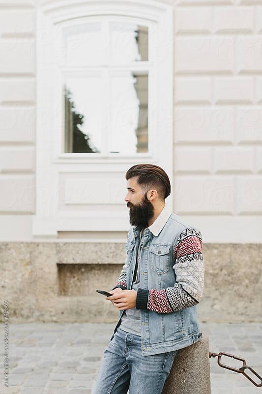 Handsome man sitting on an urban cement bollard by Amir Kaljikovic for Stocksy United