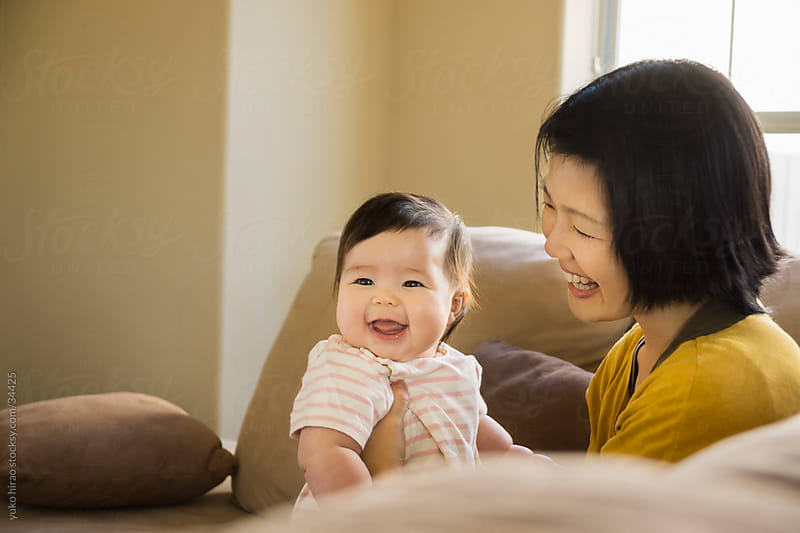 Asian mother and baby girl on a couch by yuko hirao for Stocksy United