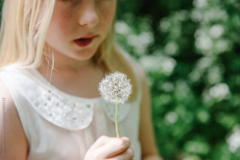 A little girl with a dandelion, thinking about making a wish by Helen Rushbrook for Stocksy United