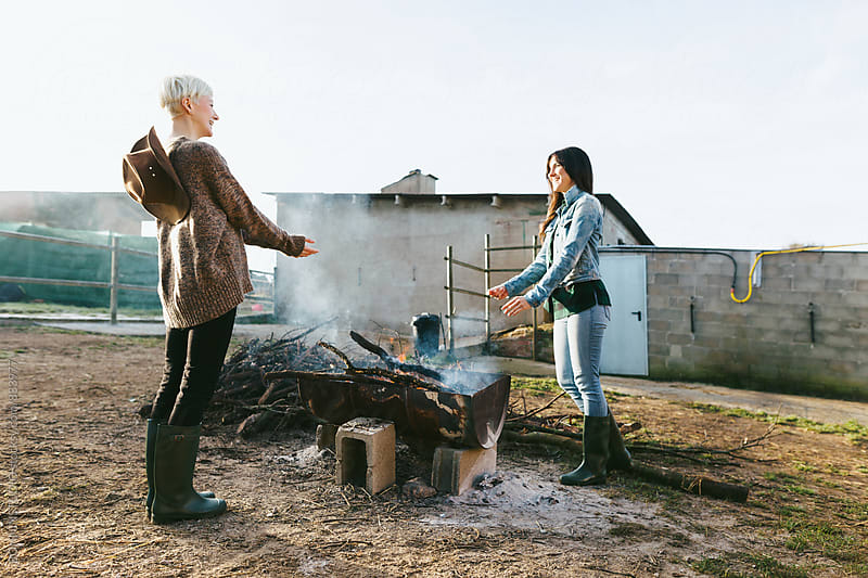 Women farmers warming their hands over a bonfire on farm. by BONNINSTUDIO for Stocksy United