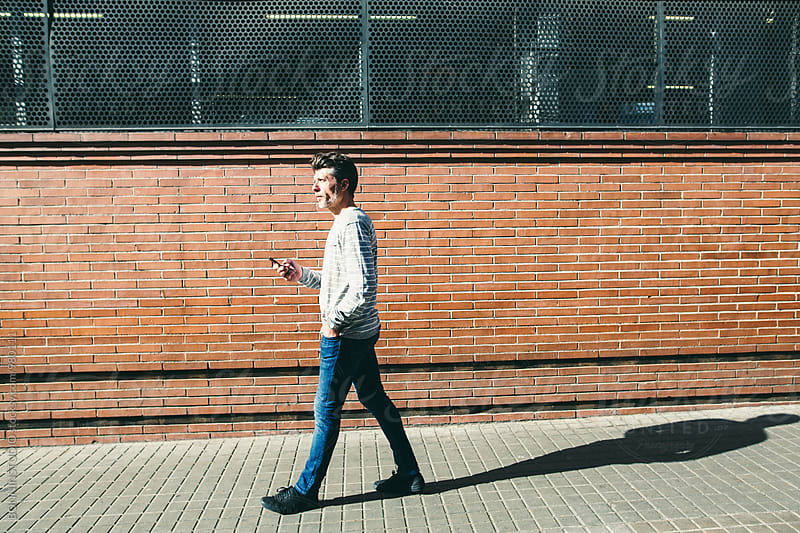 Side view of a mature man holding his phone walking in the city. by BONNINSTUDIO for Stocksy United