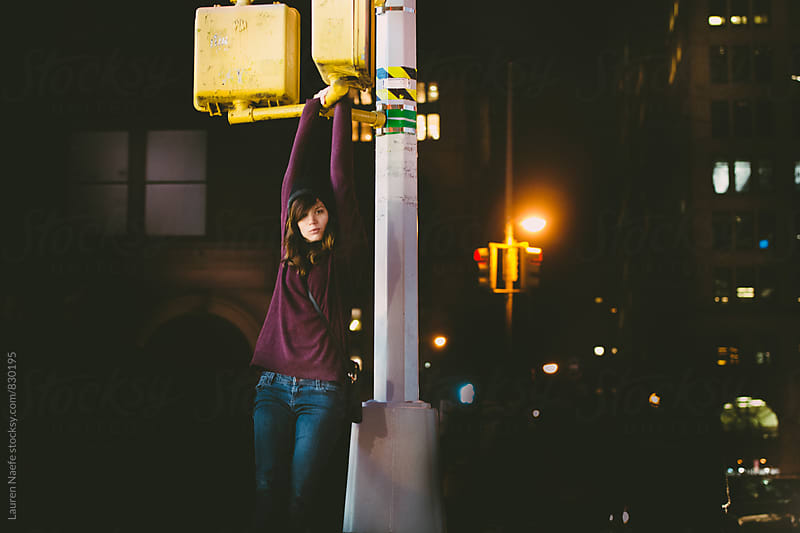 Young woman hanging out in the city at night by Lauren Naefe for Stocksy United