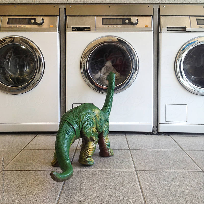 Curious dinosaur looking at washing machine. by Ivar Teunissen for Stocksy United