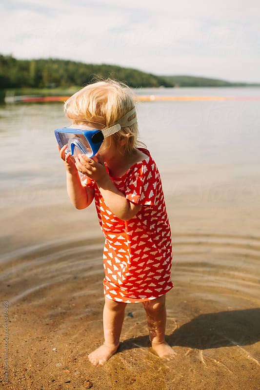 Little blonde girl stands in water holding too big goggles to her face. by Julia Forsman for Stocksy United