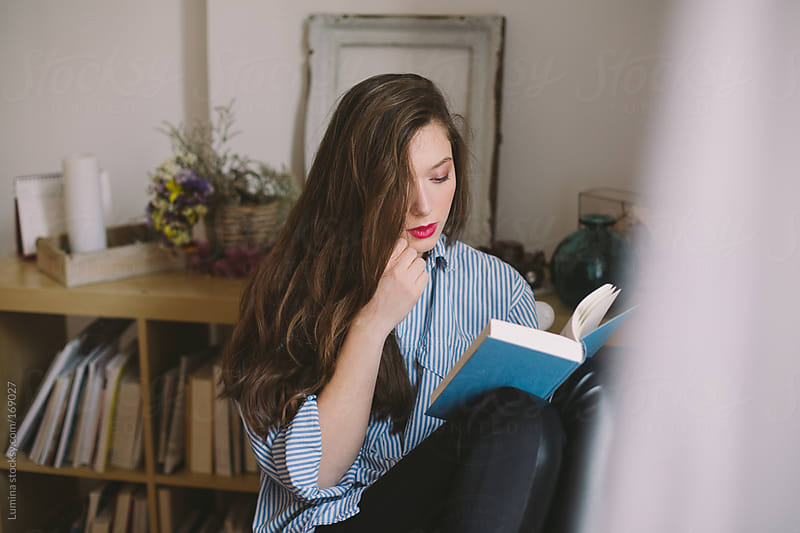Young Woman Reading a Book by Lumina for Stocksy United