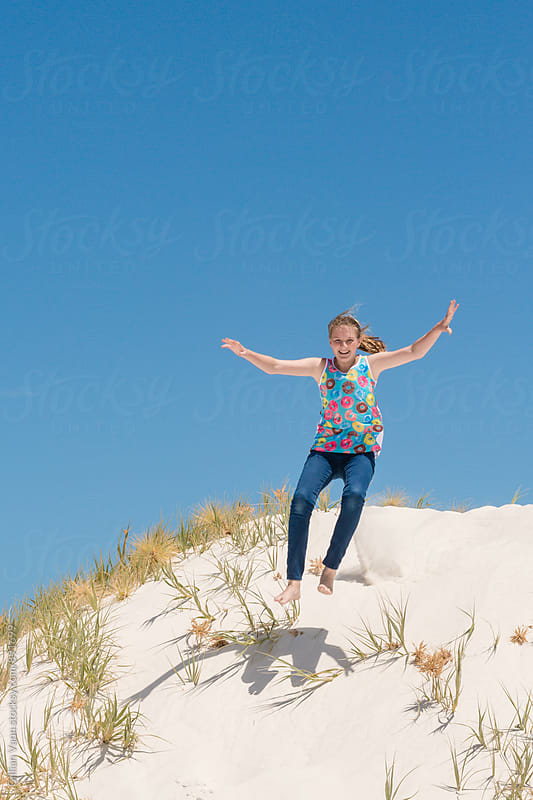 teen girl jumping the sand dunes by Gillian Vann for Stocksy United