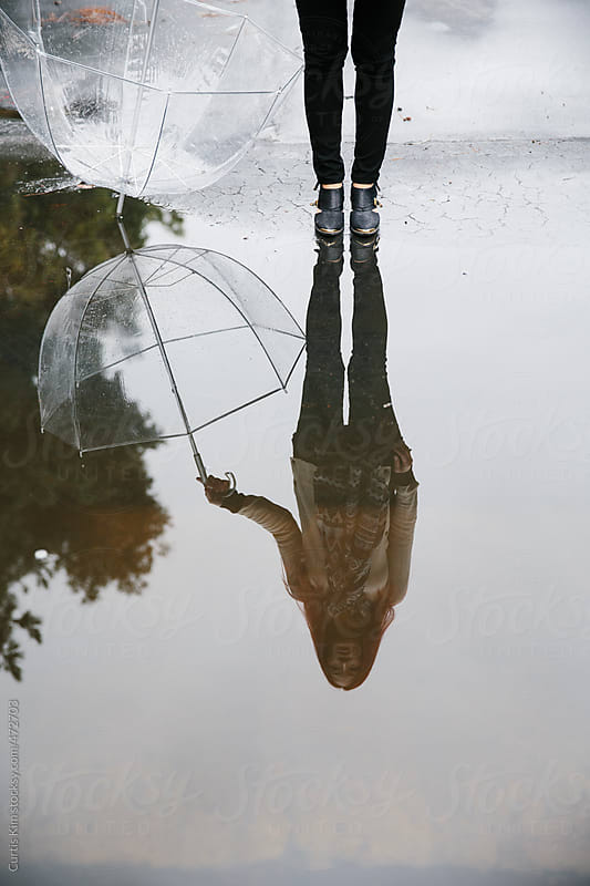 Silhouette puddle reflection of woman standing and holding umbrella by Curtis Kim for Stocksy United