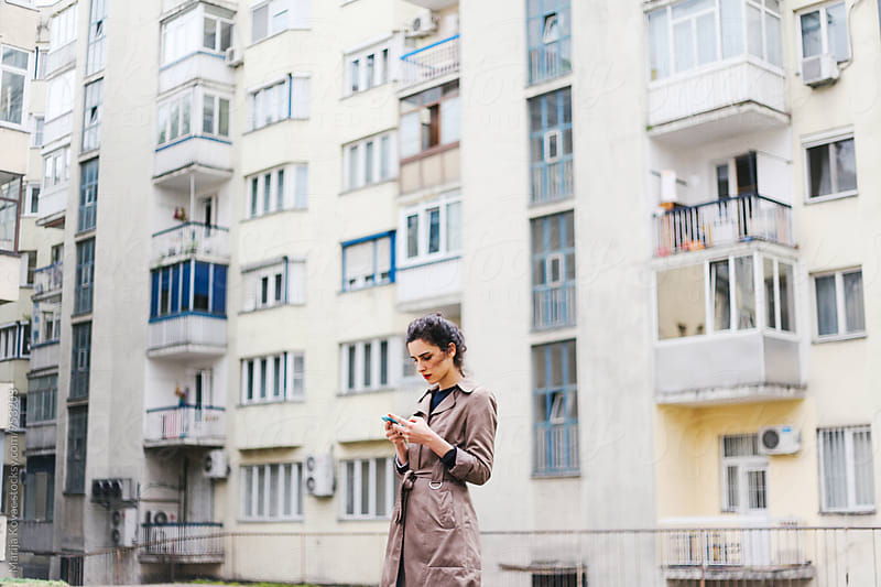 Woman looking at her smart phone by Marija Kovac for Stocksy United