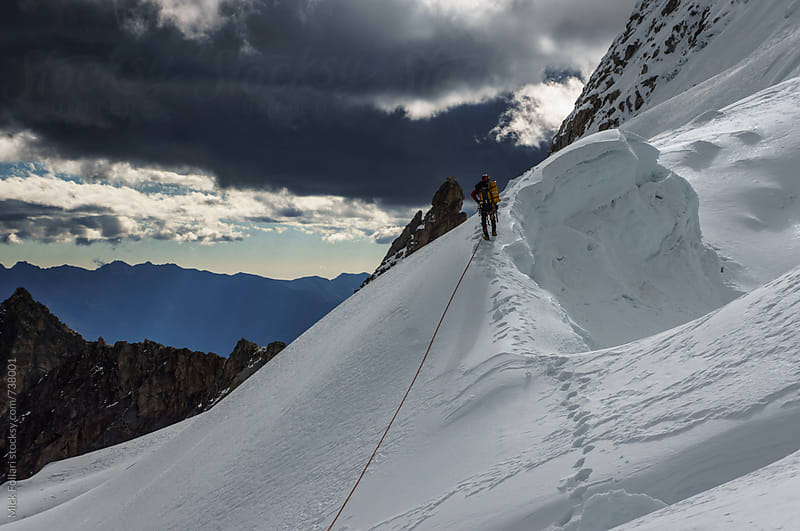 Mountain climber on a glacier with dramatic sky by Mick Follari for Stocksy United