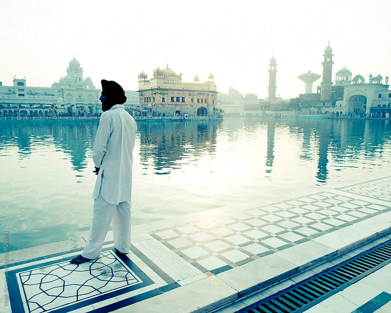 Sikh man stands by the lake of the Golden Temple. Amritsar. India by Hugh Sitton for Stocksy United