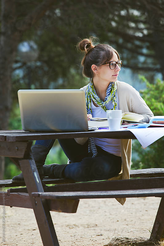 Young student woman with glasses wearing casual clothes and studying on a park. by BONNINSTUDIO for Stocksy United