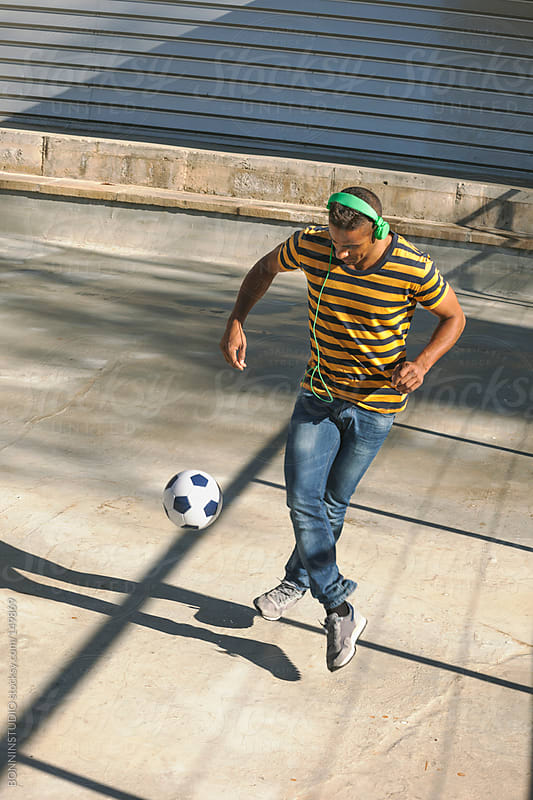 Black man playing with soccer ball on cityscape. by BONNINSTUDIO for Stocksy United