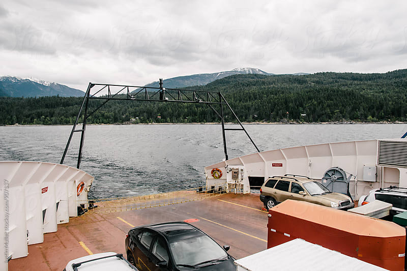 Ferry crossing a lake with a load of vehicles by Justin Mullet for Stocksy United