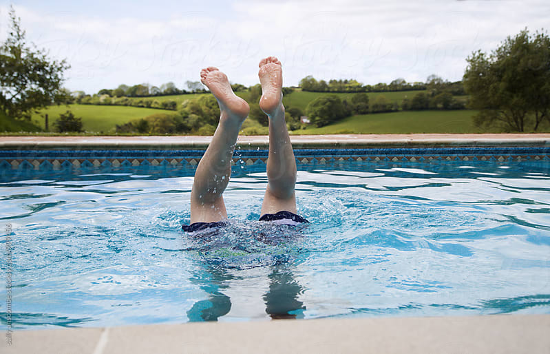 Man diving into a swimming pool by sally anscombe for Stocksy United