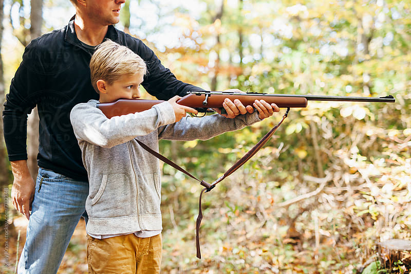 father teaching his son how to shoot a rifle  by Kelly Knox for Stocksy United