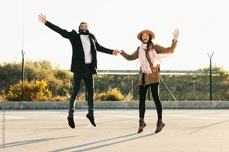 Couple jumping on a sunny winter day. by BONNINSTUDIO for Stocksy United