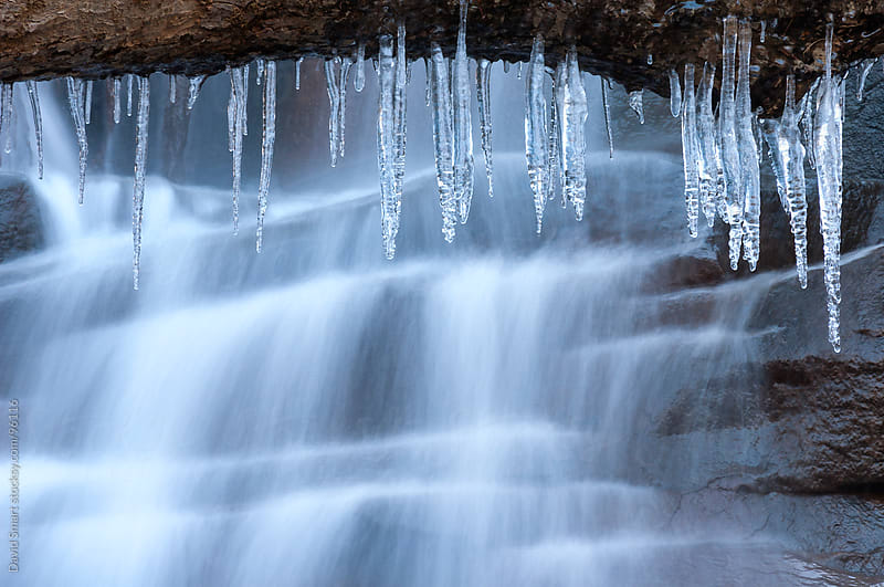 Icicles formed by frozen spray from a waterfall by David Smart for Stocksy United