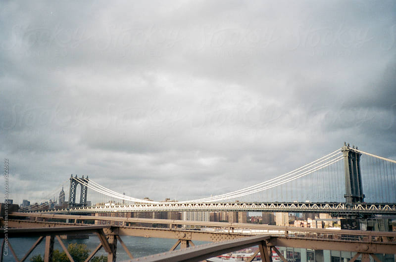 A shard of light touches the Manhattan Bridge on an otherwise gloomy day by Cameron Whitman for Stocksy United