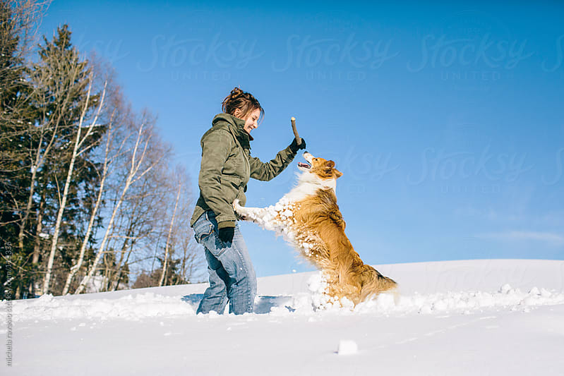 Young woman playing with her dog in the snow by michela ravasio for Stocksy United