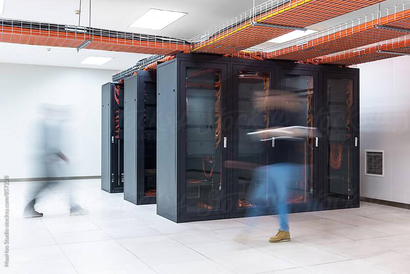 BLurred motion of people walking in a server room by MaaHoo Studio for Stocksy United