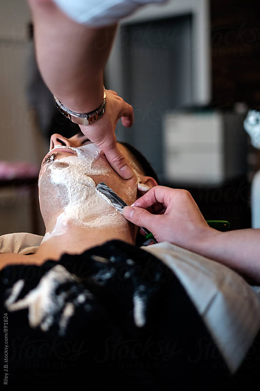 A gentleman barber shaves the cheek of a client using a straight razor. by Riley J.B. for Stocksy United