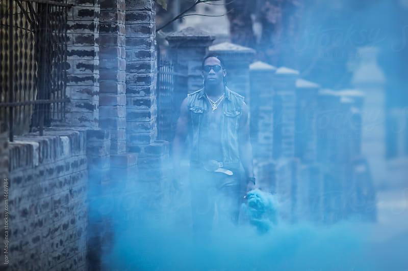 black man with blue signal stick, smoke bomb by Igor Madjinca for Stocksy United