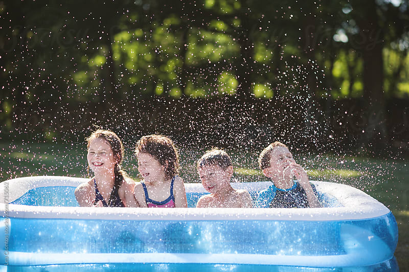 Friends having fun in an inflatable pool  by Lea Csontos for Stocksy United