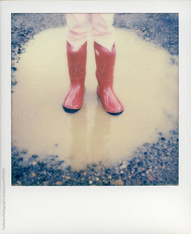 Person wearing red rubbers boots standing in a rain puddle. by Carleton Photography for Stocksy United