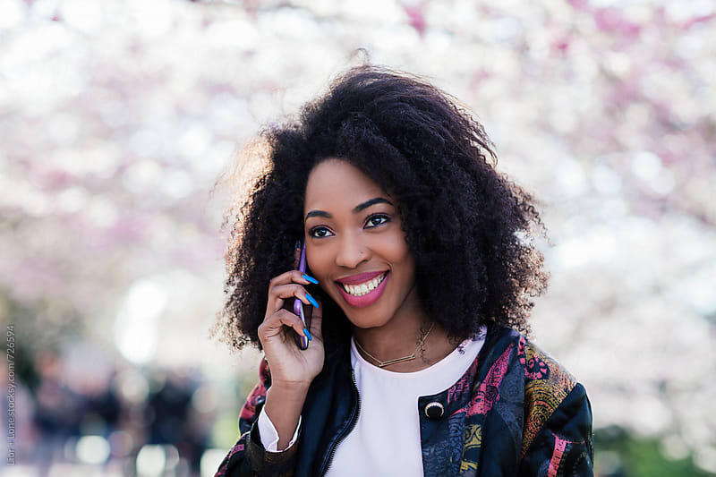 Young black woman smiling while talking on the phone by Lior + Lone for Stocksy United