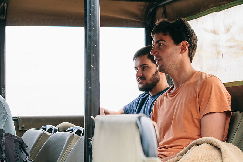 Two young men on the back of an off-road vehicle on a safari by Alejandro Moreno de Carlos for Stocksy United