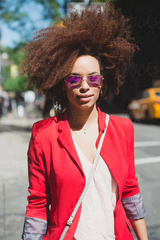 Stylish young woman crossing the street in the city by Lauren Naefe for Stocksy United