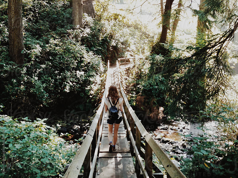 Woman Walking Across Forest Bridge by Kevin Russ for Stocksy United