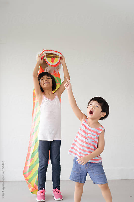 Siblings having fun playing with Chinese lion dance costume by Alita Ong for Stocksy United