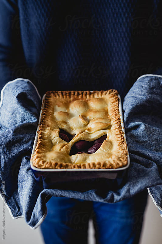 Man is holding plum pie by Tatjana Zlatkovic for Stocksy United