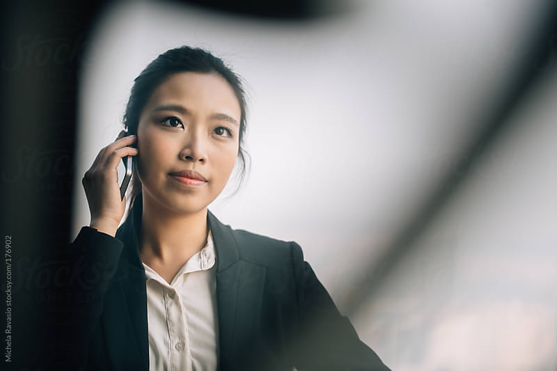 Asian businesswoman talking on her cell phone by michela ravasio for Stocksy United