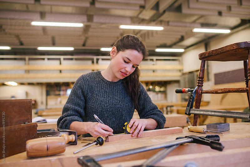 Female woodworker working on a bench  by Ivo de Bruijn for Stocksy United