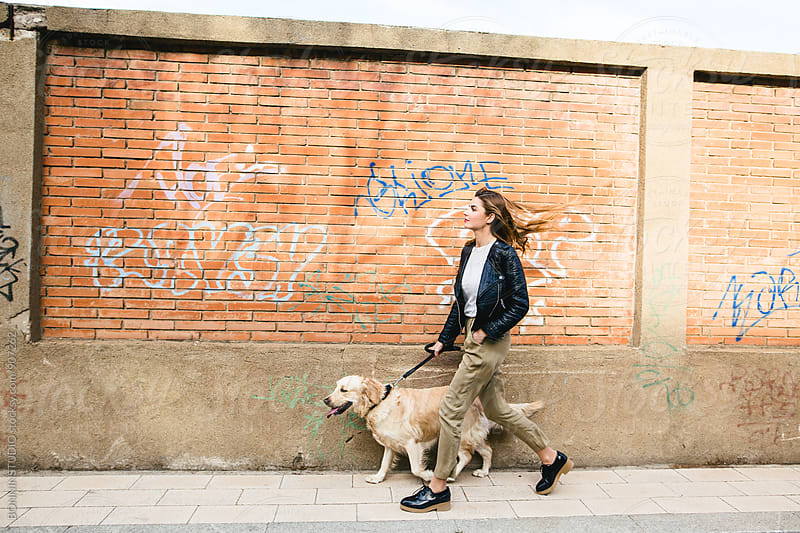 Side view of a woman walking her dog on sidewalk. by BONNINSTUDIO for Stocksy United