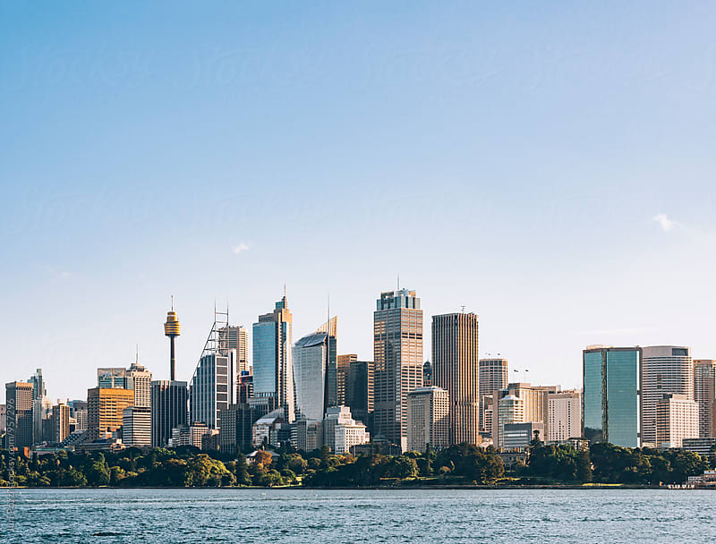 Sydney skyline seen from the bay by Juri Pozzi for Stocksy United