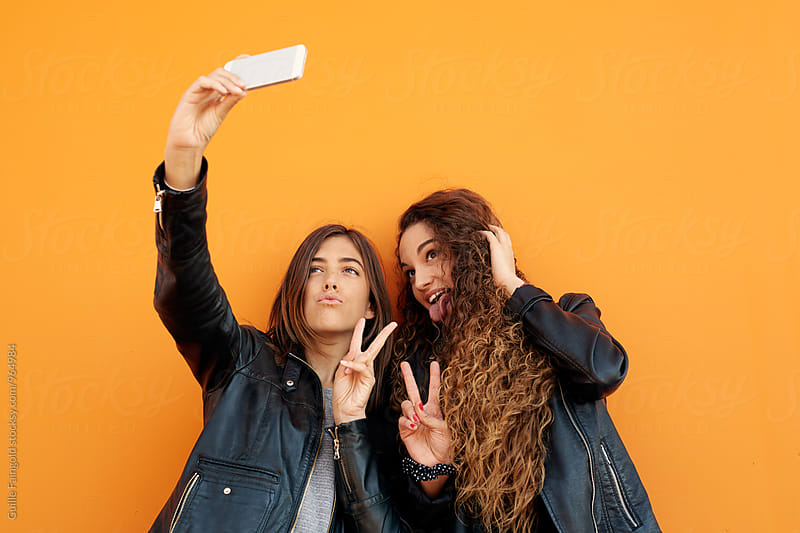 Attractive girlfriends taking selfie  by Guille Faingold for Stocksy United
