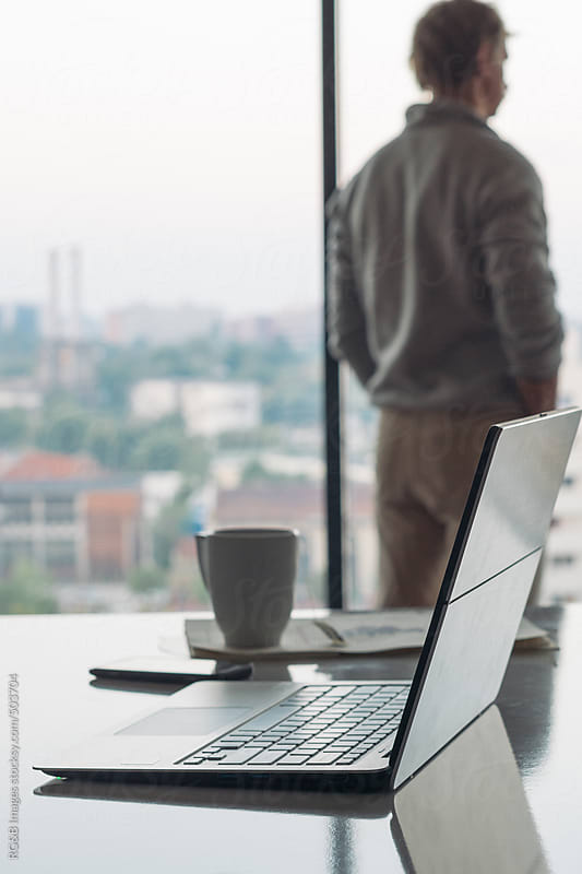 laptop with casual business man by the window  by RG&B Images for Stocksy United