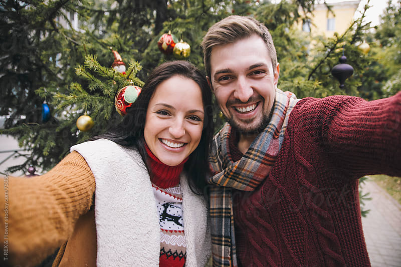 Couple taking selfie against Christmas tree by Danil Nevsky for Stocksy United