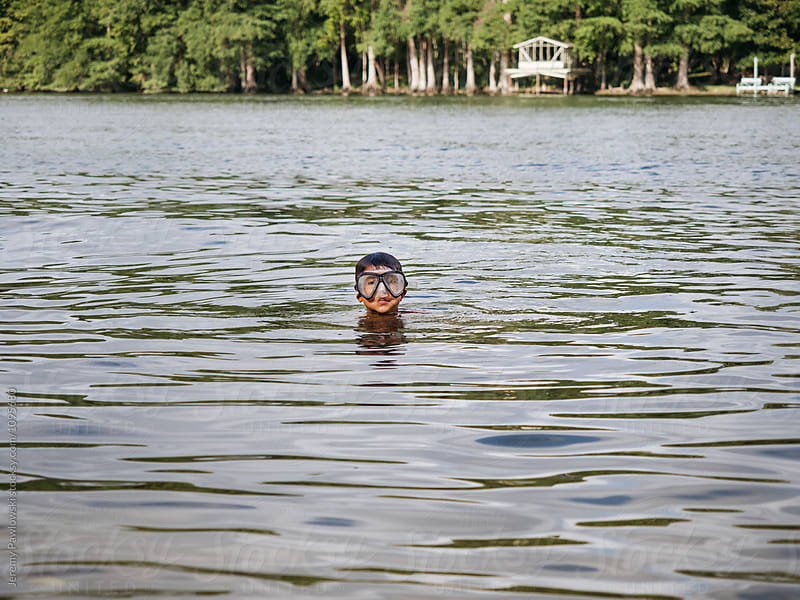 Young boy swimming in lake while wearing scuba mask. by Jeremy Pawlowski for Stocksy United