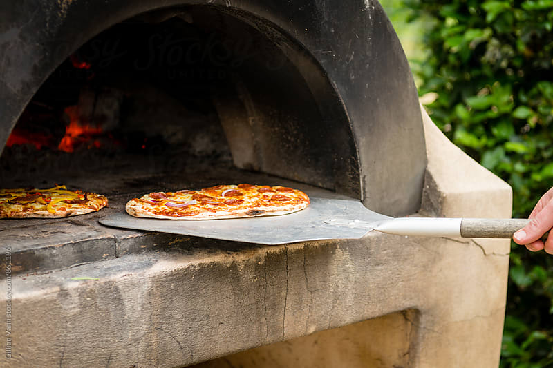 cooking pizza in an outdoor wood fired pizza oven by Gillian Vann for Stocksy United